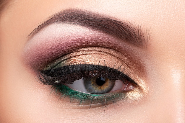 Close up van mooie vrouw oog met veelkleurige smokey eyes make-up. moderne mode-make-up. Premium Foto