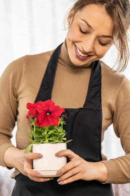 Close-up van mooie vrouwelijke tuinman houdt keramische pot met bloeiende petunia's in handen, focus op bloemen, gelukkige jonge vrouw bloemist groeiende bloemen, huistuin, tuinieren hobby, bloementeelt Premium Foto