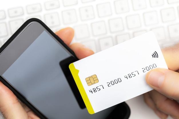 Close-up van online klant betalen met creditcards met smartphone op computertoetsenbord met kopie ruimte. online winkelen. Premium Foto