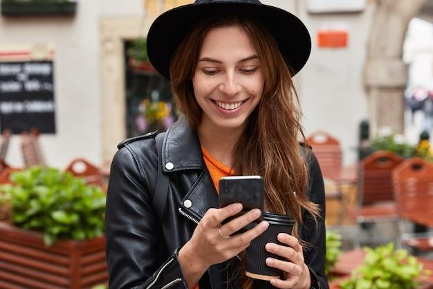 Close-up van opgetogen jonge vrouw maakt gebruik van de internetverbinding van mobiele telefoongegevens, leest tekstbericht Gratis Foto