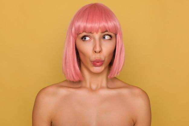 Close-up van opgewonden jonge mooie dame met kort roze haar die haar lippen vouwt terwijl ze verward opzij kijkt, poseren over mosterdmuur met blote schouders Gratis Foto