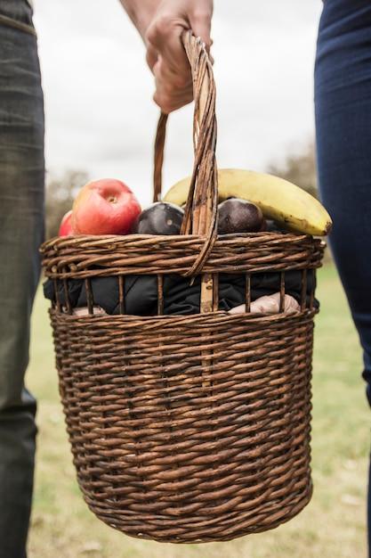 Close-up van paar hand picknickmand vol met fruit te houden Gratis Foto
