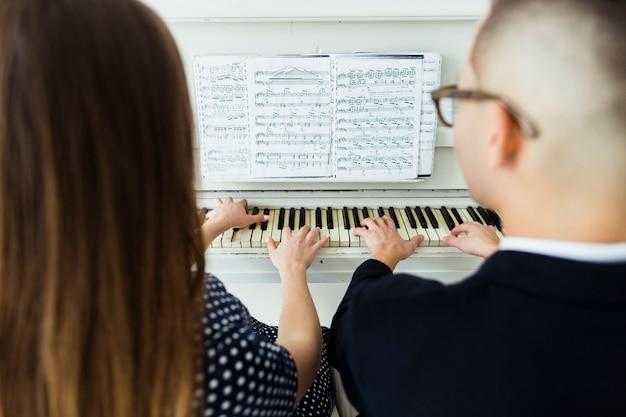 Close-up van paar pianospelen met muzikale blad Gratis Foto