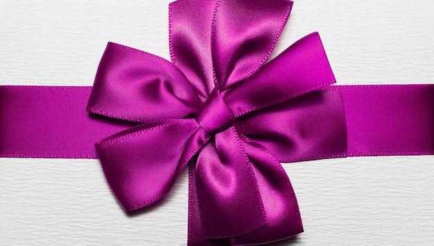 Close-up van paars inwikkeling lint in vorm van boog voor witte geschenkdoos Premium Foto