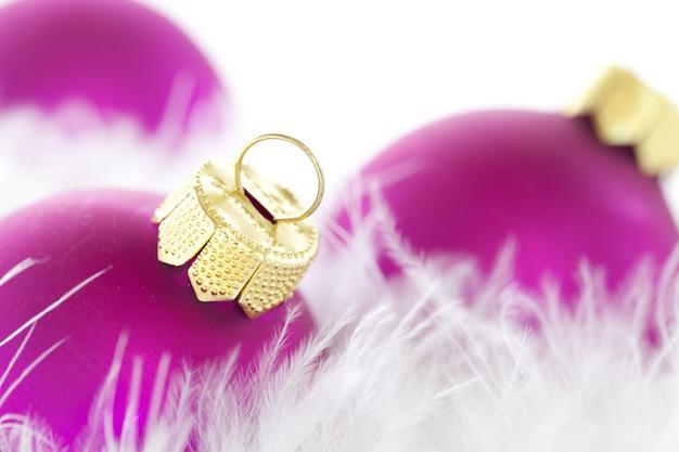 Close-up van paarse kerst ornamenten en veren onder de lichten met een onscherpe achtergrond Gratis Foto
