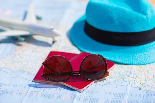 Close-up van paspoorten, speelgoedvliegtuig, zonnebril op de kaart Premium Foto