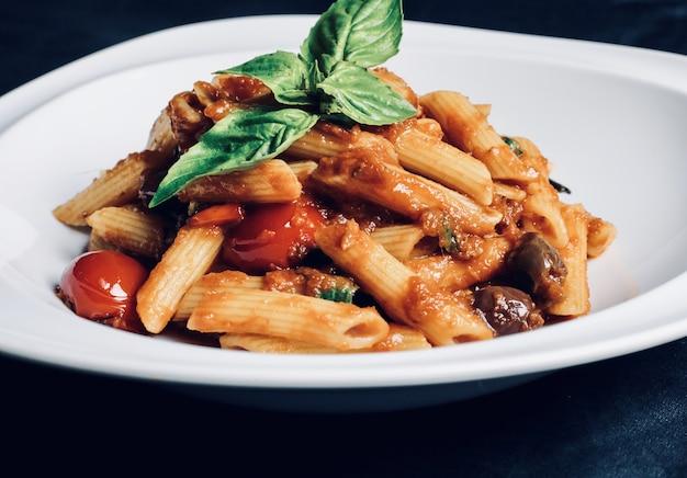 Close-up van pasta met sauzen en vlees in een kom op tafel onder de lichten Gratis Foto