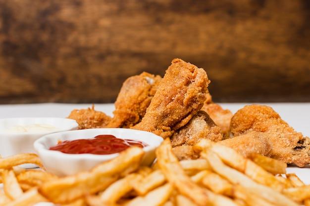 Close-up van patat en gebakken kip Gratis Foto