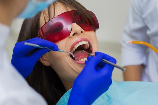 Close-up van patiënt die procedure met tandartsen krijgt Gratis Foto