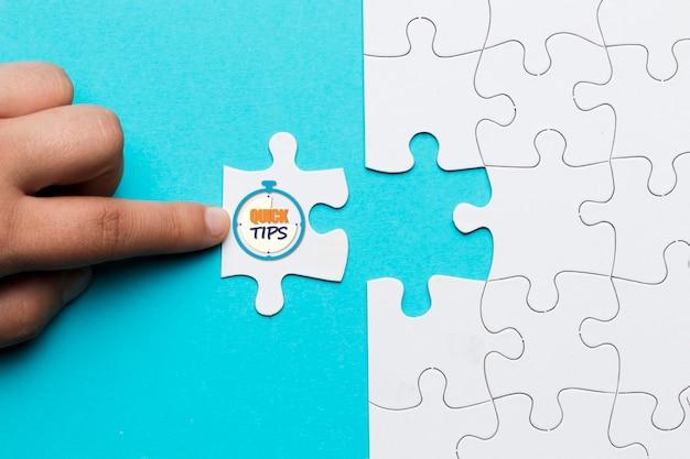 Close-up van persoon aanraken witte puzzel met snelle tips tekst op stopwatch klok Gratis Foto