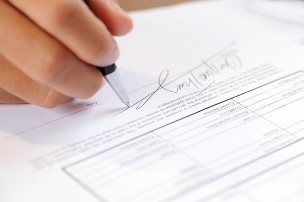 Close-up van persoon die document met ballpoint ondertekent Gratis Foto