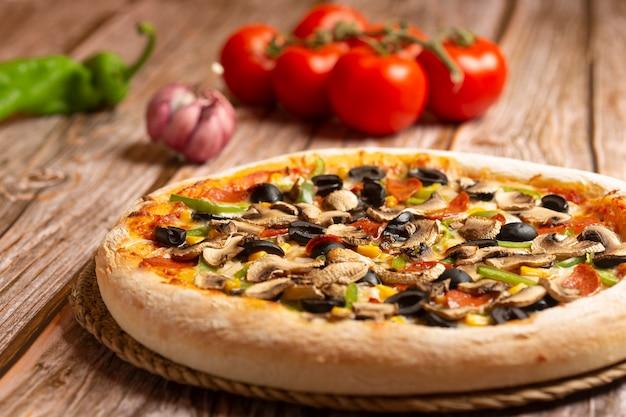 Close-up van pizza met groenten en pepperoni op houten Premium Foto