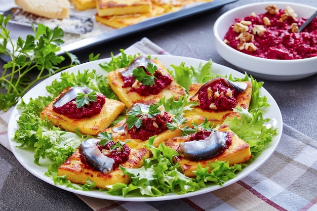 Close-up van polenta vierkanten met romige bietenpuree, gegarneerd met ansjovis en peterselie op een witte plaat. vers gebakken polentabars en parmezaanse kaas op een bakplaat op een betonnen tafel Premium Foto