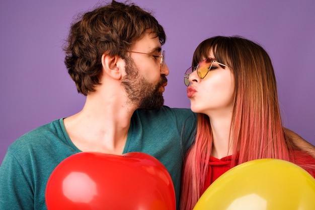 Close-up van portret van gelukkige hipster paar op zoek naar elkaar en proberen te kussen, ballonnen, heldere trendy vrijetijdskleding en glazen, romantische sfeer te houden Gratis Foto