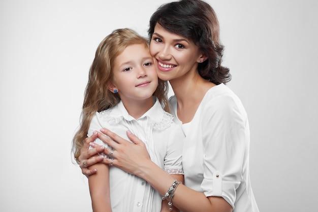 Close-up van prachtige familie paar: mooie moeder en haar dochtertje. ze zijn erg blij met een mooie glimlach. ze dragen witte t-shirts. Gratis Foto