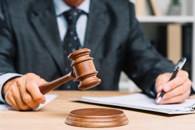 Close-up van rechter die oordeel geven door hamer bij bureau te raken Gratis Foto