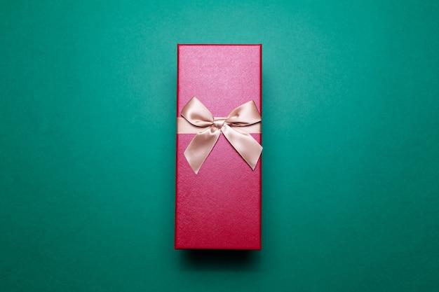 Close-up van rode geschenkdoos met gouden strik op oppervlak van groene kleur Premium Foto