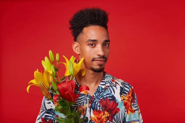 Close-up van rustige jonge afro-amerikaanse man, draagt in hawaiiaans shirt, kijkt naar de camera, houdt gele en rode bloemen, staat op rode achtergrond. Gratis Foto