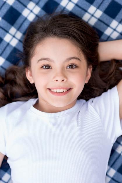 Close-up van schattig aantrekkelijk meisje liggend op deken Gratis Foto