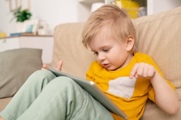 Close-up van schattige jongen zittend op de bank en praten met ouders via telecommunicatie-app op tablet in de woonkamer Premium Foto
