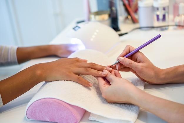 Close-up van schoonheidsspecialist die de spijkers van een vrouw met een borstel in een spijkersalon schildert Gratis Foto