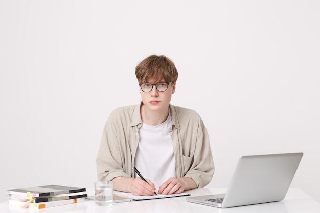 Close-up van serieuze knappe jongeman student draagt een beige overhemd en bril zitten met laptop en notebooks aan de tafel en schrijven geïsoleerd over witte muur Gratis Foto