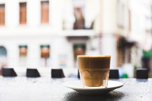 Close-up van smakelijke koffiekop met schotel op bureau Gratis Foto