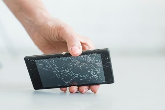Close-up van smartphone van de de handholding van de vrouw met het gebarsten scherm Gratis Foto