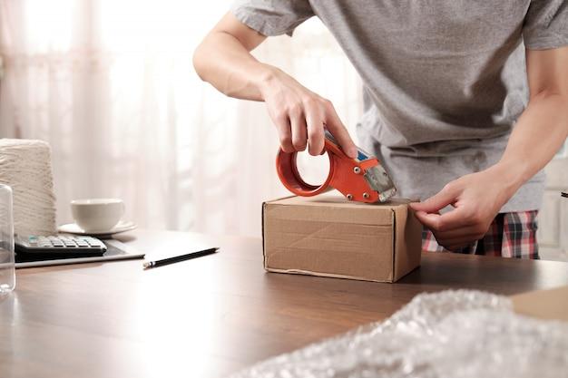 Close-up van startup ondernemer verpakking kartonnen doos. over online winkelen. Premium Foto