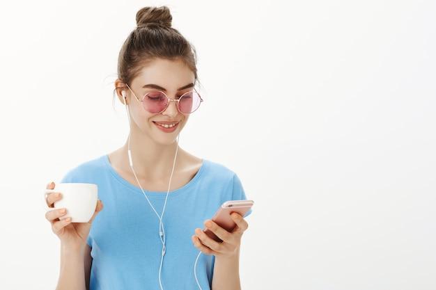 Close-up van stijlvolle vrouwelijke vrouw in zonnebril, luisteren naar podcast of muziek, kopje koffie drinken, smartphone houden Gratis Foto