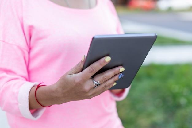 Close-up van tablet worden gebruikt door vrouw op zomer straat. achteraanzicht. Premium Foto