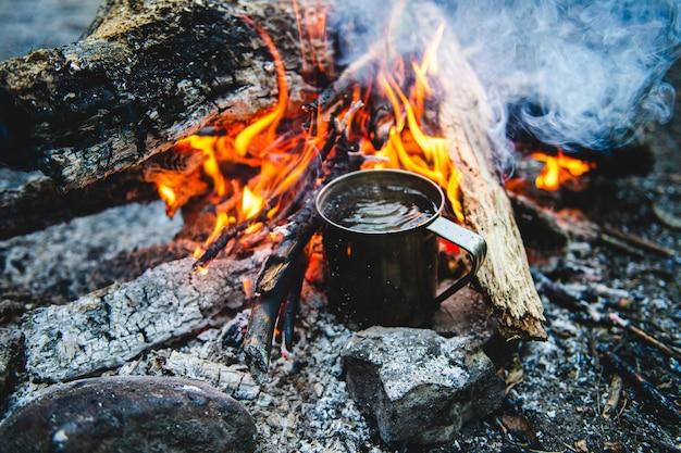 Close-up van thee in metalen mok warmt op in vreugdevuur Premium Foto