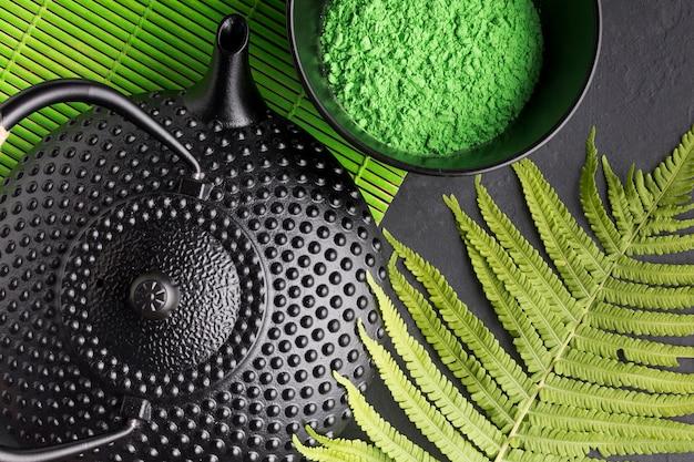 Close-up van theepot met groene match tea poeder en fern verlaat Gratis Foto