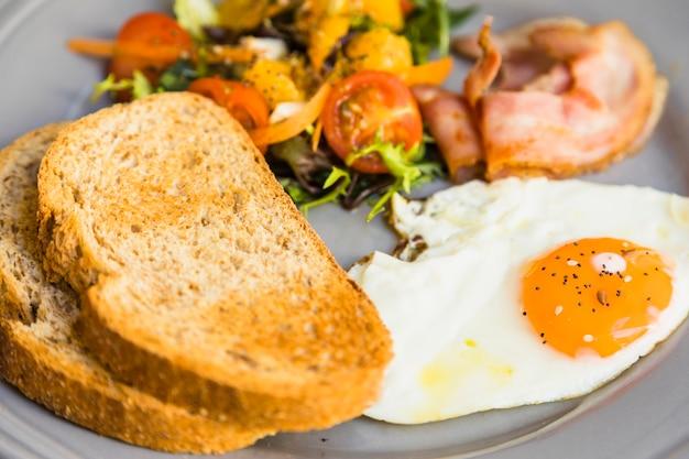Close-up van toast; gebakken eieren; salade en spek op grijze keramische plaat Gratis Foto