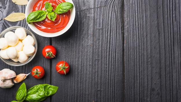 Close-up van tomatensaus met mozarella; pasta; knoflook een basilicum op houten plank Gratis Foto