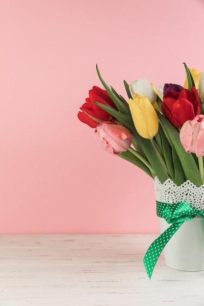 Close-up van tulpen in de witte vaas met groene strik op houten bureau tegen roze achtergrond Gratis Foto