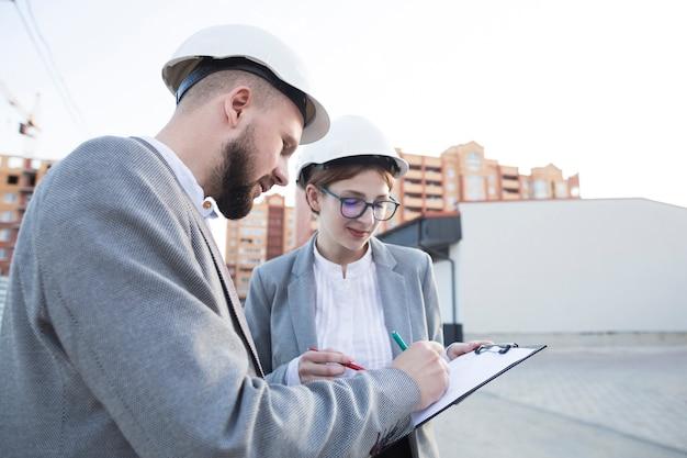 Close-up van twee architect die bij bouwwerf samenwerken Gratis Foto