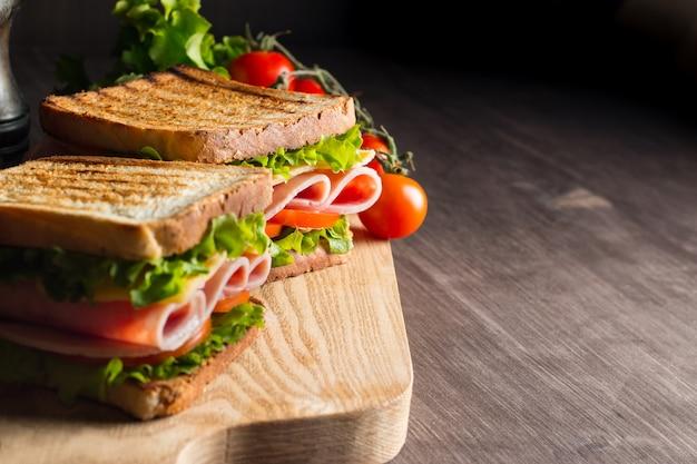 Close-up van twee broodjes met spek, salami, prosciutto en verse groenten op rustieke houten snijplank. club sandwich concept. Premium Foto