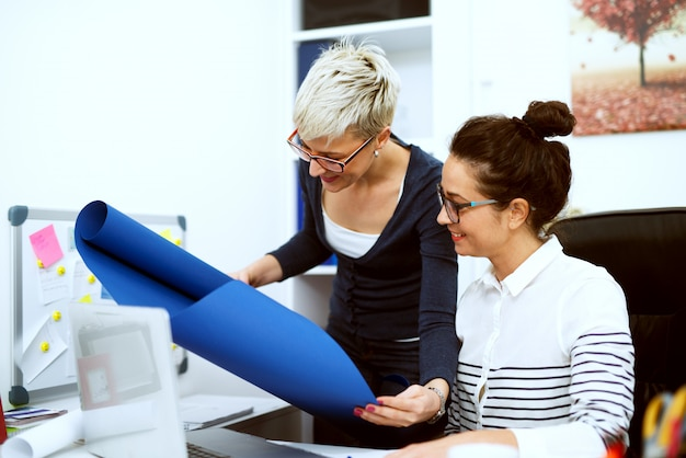 Close-up van twee glimlachende gerichte stijlvolle zakelijke vrouwen van middelbare leeftijd die samenwerken aan het project op kantoor. Premium Foto