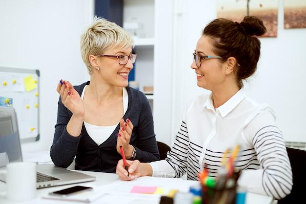 Close-up van twee glimlachende stijlvolle zakelijke vrouwen van middelbare leeftijd die werken en een gesprek voeren terwijl ze in het kantoor naast elkaar zitten. Premium Foto