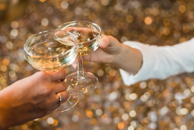 Close-up van twee handen die whisky roosteren Gratis Foto