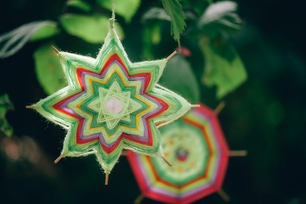 Close-up van twee handgemaakte mandala's van wollen draden die op boomtakken hangen in het de herfstbos Premium Foto