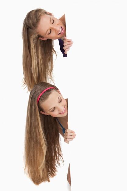 Close-up van twee lachende lang haar studenten achter een leeg bord Premium Foto