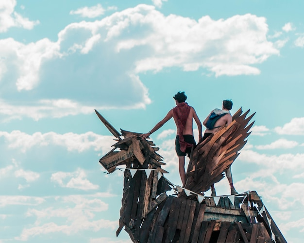 Close-up van twee mannen die zich op een eenhoornstandbeeld bevinden dat van planken van hout tegen een bewolkte hemel wordt gemaakt Gratis Foto
