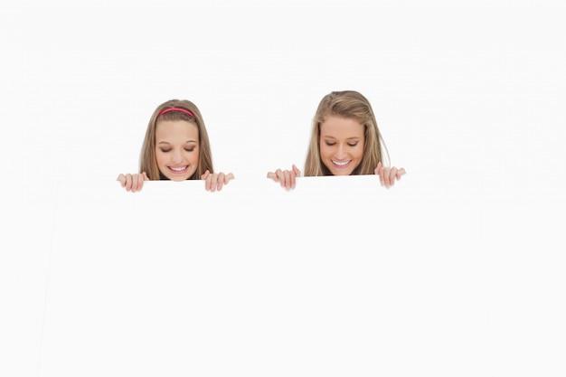Close-up van twee studenten achter een leeg teken Premium Foto