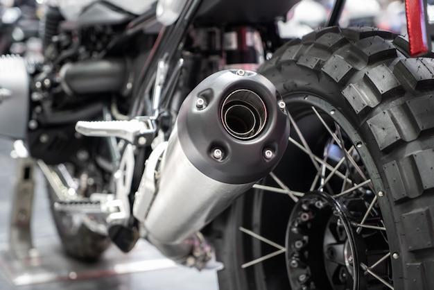 Close-up van uitlaat of inname van zwarte sport racen motorfiets met nieuwe band en wiel in de showroom. lage hoek foto van motorfiets. Premium Foto
