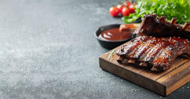 Close-up van varkensvleesribben die met bbq saus worden geroosterd. Premium Foto