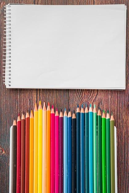 Close-up van veelkleurige potlood en witte spiraal notitie boek op houten bureau Gratis Foto