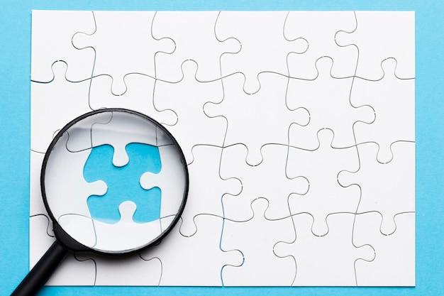 Close-up van vergrootglas op ontbrekende puzzel over blauwe achtergrond Gratis Foto