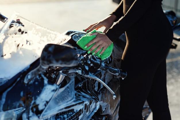 Close-up van verleidelijke jonge vrouw hand wassen stijlvolle sport motorfiets en veegt het van roze Premium Foto